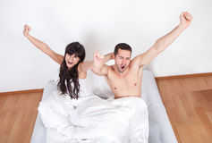 Couple waking up in bed. Lovely young couple waking up in bed at home Stock Image