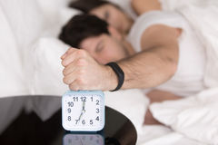 Couple waking up early, guy turning off annoying alarm clock. Couple awakened by alarm clock in bed at home, guy lying on bed annoyed by noisy alarm clock in the Royalty Free Stock Photo