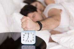 Couple waking up early, guy turning off annoying alarm clock Royalty Free Stock Photo