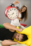 Couple waking up in the morning. Beautiful Young couple sleeping in bed in the morning. Sleepy boyfriend waking up with alarm clock Royalty Free Stock Photo