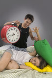 Couple waking up in the morning. Beautiful Young couple sleeping in bed in the morning. Sleepy boyfriend waking up with alarm clock Royalty Free Stock Image