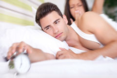 Couple Waking up to Alarm. Young snoozing couple in bed waking up to alarm clock Royalty Free Stock Photography