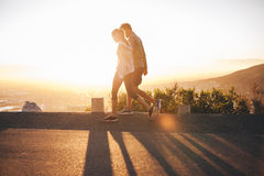 Couple walk along road at sunrise Royalty Free Stock Photo