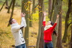 Couple on a walk in autumn park throwing leaves Royalty Free Stock Photos