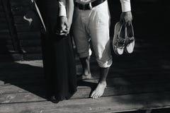 Couple walk barefoot on pier Stock Photos