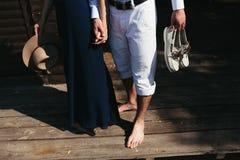 Couple walk barefoot on pier Stock Photo