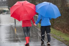 Couple walk hand in hand through the rain. Royalty Free Stock Photos