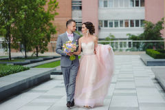 Couple walk holding hands, looking at each other Royalty Free Stock Photos