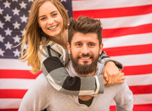 Couple on walk. Portrait of a young happy couple on the background of the US flag Stock Photography