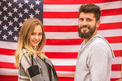 Couple on walk. Portrait of a young happy couple on the background of the US flag Royalty Free Stock Photo