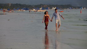Couple walk together along the beach at sunset. Young couple walking on the beach hand in hand, playing with water, the sunset behind the sailing boats and stock video