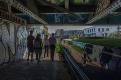 Couple walk under a bridge on the River Lea London. Couple walk under a bridge on the River Lea Navigation, Hackney Wick, East London, England, United Kingdom stock image