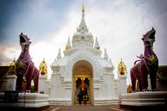 The couple walked to the door of Wat Phra That Hariphunchai. The. Re is a statue of lion brown Royalty Free Stock Photo