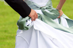 Couple Walking. Newlyweds walking on grass with groom helping to hold up bride's wedding dress Stock Photography