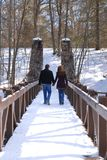 Couple Walking Across A Bridge Holding Hands. Newly engaged couple in their twenties, holding hands and walking across a pedestrian bridge over a river in winter Stock Images