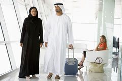 Couple walking through airport departure lounge Stock Photo
