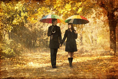 Couple walking at alley in autumn park. Photo in old image style Royalty Free Stock Photography