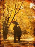 Couple walking at alley in autumn park. Photo in old image style Royalty Free Stock Image