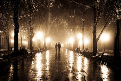 Couple walking at alley in night lights. Photo in vintage yellow style #15 Stock Images