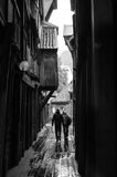 Couple walking through an alley in the rain Royalty Free Stock Image