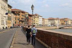 Couple walking along the Arno river in Pisa, Italy Stock Photo