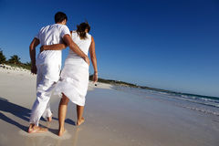 Couple walking along beach Stock Images