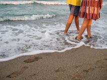 Couple walking along beach Stock Photos