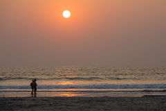 Couple walking along the beach at sunset. Silhouette of a couple walking along the seashore at sunset of the day. India, Goa-January 12, 2017. Morjim Beach Stock Image