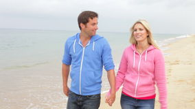 Couple Walking Along Beach Together. Couple walking towards camera along autumn beach holding hands. Shot on Canon 5d Mk2 with a frame rate of 30fps stock footage