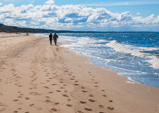 Couple is walking along the beach under blue sky Royalty Free Stock Image