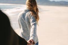 Couple walking along the beach stock photography