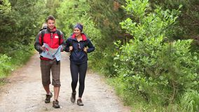 Couple walking along a country trail looking at map Stock Images