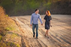 Couple walking along the dirt road. Young happy couple walking along the dirt road Royalty Free Stock Image