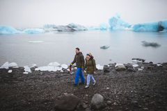 Couple Walking Along Lake Shore. With ice stock photography