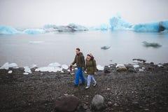 Couple Walking Along Lake Shore. With ice Stock Photography