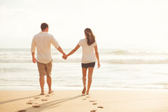 Couple Walking along the Ocean at Sunset Stock Images