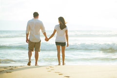 Couple Walking along the Ocean at Sunset Stock Photography