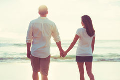 Couple Walking along the Ocean at Sunset Royalty Free Stock Photo