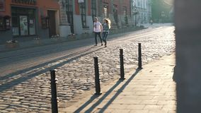 The couple is walking along old city stock video