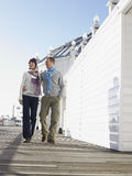 Couple Walking Along Pier Royalty Free Stock Photography