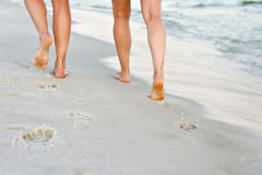 Couple walking along the sandy beach Stock Photography