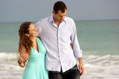 Couple walking along the seaside  with their arms. Young couple walking along bonita beach in florida at the gulf of mexico having a discussion with waves Stock Image