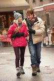 Couple Walking Along Snowy Street. Couple Walking Along Snowy Town Street In Ski Resort Stock Photo