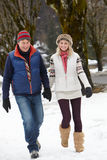 Couple Walking Along Snowy Street In Ski Resort. Holding hand Stock Images