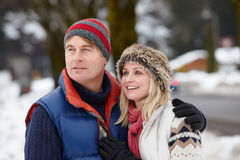 Couple Walking Along Snowy Street In Ski Resort. Looking into the distance Stock Photo
