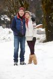 Couple Walking Along Snowy Street In Ski Resort. Hugging and smiling at camera Royalty Free Stock Image