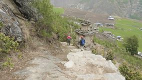 Couple walking along the stairs on the trek around Manaslu, village Prok, Nepal.