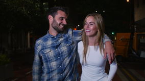 Couple Walking Along Street On Night Out. Couple walking towards camera on night out in city.Shot in 4k on GH4 at frame rate of 25fps stock footage