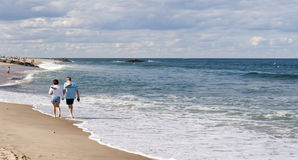 Couple Walking Along The Beach Royalty Free Stock Photo