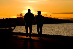 Couple Walking Along Waterfront At Sunset Royalty Free Stock Photo